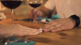 Mano femenina que toca la mano masculina mientras que cena romántica en la igualación del restaurante Mujer que toca al novio de  almacen de video