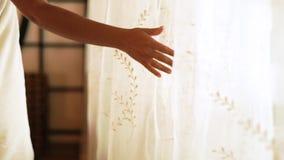 Mano femenina que toca las cortinas blancas en dormitorio acogedor Mujer joven envuelta en toalla de baño en interior del dormito metrajes