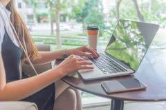 Mano femenina usando el ordenador portátil con café y el teléfono elegante por otra parte Imagen de archivo libre de regalías