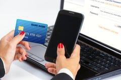 Mano femenina, usando la tarjeta de Internet para las e-actividades bancarias fotos de archivo libres de regalías
