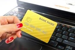 Mano femenina, usando la tarjeta de Internet para las e-actividades bancarias foto de archivo
