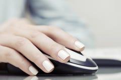 Mano femenina usando ratón del ordenador Imagen de archivo