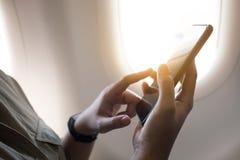 Mano femenina usando smartphone en el avión con la ventana imagen de archivo libre de regalías