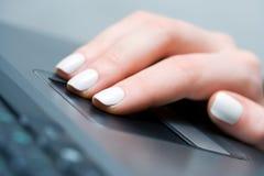 Mano femenina usando touchpad. Foto de archivo