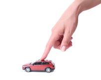 Mano femenina y el coche del juguete Fotos de archivo