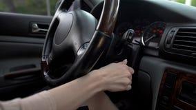 Mano femminile che avvia il motore dell'automobile, donna di affari che conduce veicolo di lusso, fine su immagini stock