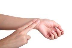 Mano femminile che controlla impulso su fondo bianco Fotografia Stock