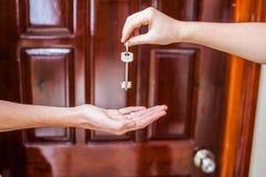 Mano femminile che dà ad una chiave alla casa una mano del ` s dell'uomo su un fondo di una porta di legno Possesso del concetto  immagini stock libere da diritti