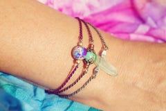 Mano femminile che indossa i braccialetti di pietra naturali della perla immagini stock