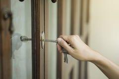 Mano femminile che mette chiave della casa nella serratura di entrata principale della casa fotografia stock libera da diritti