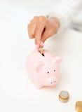 Mano femminile che mette le euro monete nel porcellino salvadanaio Immagini Stock