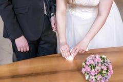 Mano femminile che prende fede nuziale dalla scatola per lo sposo durante la cerimonia Immagine Stock