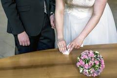 Mano femminile che prende fede nuziale dalla scatola per lo sposo durante la cerimonia Fotografia Stock Libera da Diritti