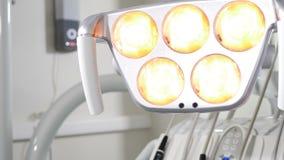 Mano femminile che regola illuminazione dentaria del LED prima dell'operazione, degli strumenti del dentista e dell'ottenere prof archivi video