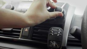 Mano femminile che regola la manopola del volume di musica in automobile video d archivio