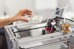 Mano femminile che rimuove il modello della casa dalla stampante 3D Fotografia Stock