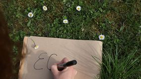 Mano femminile che scrive ECO sulla carta che pone l'erba verde della molla video d archivio