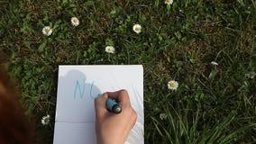 Mano femminile che scrive NO sulla carta che pone l'erba verde della molla stock footage