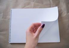 Mano femminile che sfoglia uno strato bianco dell'album di disegno immagini stock libere da diritti