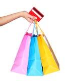 Mano femminile che tiene i sacchetti della spesa variopinti e la carta di credito Fotografia Stock Libera da Diritti