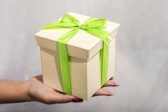 mano femminile che tiene il contenitore di regalo verde e giallo con un arco Fotografia Stock Libera da Diritti