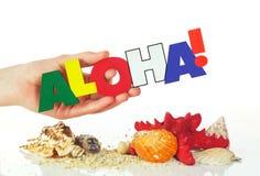 Mano femminile che tiene parola variopinta Aloha Fotografia Stock
