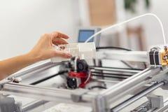 Mano femminile che tiene un modello della casa sopra la stampante 3D Fotografia Stock Libera da Diritti