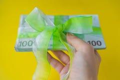 Mano femminile che tiene un pacchetto di cento euro banconote con il arco-nodo, il regalo o i dividendi verdi concetto, soldi di  fotografia stock