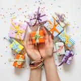 Mano femminile che tiene un piccolo regalo Regalo avvolto in carta Piccolo g Fotografie Stock