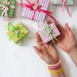 Mano femminile che tiene un regalo Regalo imballato in carta rosa colorato Immagine Stock