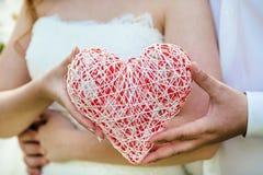 Mano femminile che tiene un simbolo del cuore Fotografia Stock