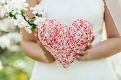 Mano femminile che tiene un simbolo del cuore Fotografie Stock Libere da Diritti