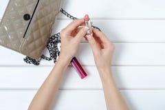 Mano femminile che tiene una borsa con rossetto Fotografia Stock