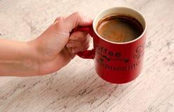 Mano femminile che tiene una tazza di caffè sopra fondo di legno fotografia stock