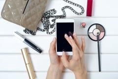 Mano femminile che tiene uno smartphone cosmetico del telefono cellulare della borsa Fotografia Stock Libera da Diritti