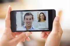 Mano femminile che tiene uno smartphone durante il video dello skype fotografia stock
