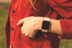 Mano femminile con gli orologi astuti in tasca del rivestimento rosso Fotografia Stock