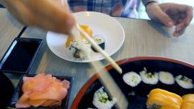 Mano femminile con i bastoncini che prendono Rolls ed i sushi dall'insieme archivi video