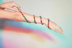 Mano femminile con i braccialetti Fotografia Stock