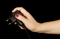 Mano femminile con il caricatore del telefono cellulare isolato sui precedenti neri Immagine Stock