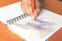 Mano femminile con il labirinto di scrittura della penna sul taccuino Fotografie Stock Libere da Diritti