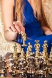 Mano femminile con il manicure elegante dell'oro che tiene pezzo degli scacchi immagine stock libera da diritti