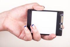 Mano femminile con l'azionamento dello SSD su bianco Fotografia Stock