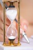 Mano femminile con l'orologio della sabbia e della penna Fotografie Stock