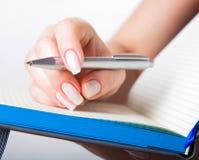 Mano femminile con la penna ed il taccuino Fotografia Stock