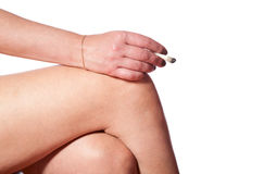 Mano femminile con la sigaretta sul ginocchio Immagini Stock Libere da Diritti
