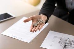 Mano femminile con le chiavi su, affare della proprietà del bene immobile Fotografia Stock Libera da Diritti