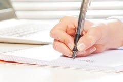 Mano femminile con scrittura della penna stilografica sul taccuino Fotografia Stock