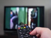 Mano femminile con telecomando sui precedenti della TV fotografia stock