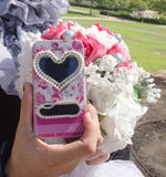 Mano femminile con un mazzo della sposa e di un telefono cellulare con un simbolo del cuore Immagine Stock